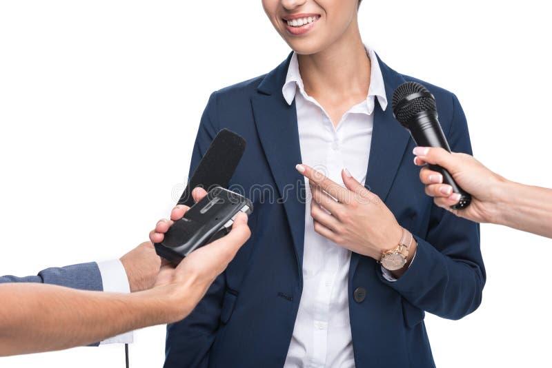 καλλιεργημένη άποψη των δημοσιογράφων με τα μικρόφωνα και του οργάνου καταγραφής που παίρνει συνέντευξη από τη χαμογελώντας επιχε στοκ φωτογραφίες με δικαίωμα ελεύθερης χρήσης