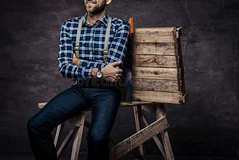 Καλλιεργημένη εικόνα Εργαζόμενος, ξυλουργός, handyman άτομο που φορά ένα ελεγμένο πουκάμισο με suspenders που κάθονται σε ξύλινα  στοκ εικόνα με δικαίωμα ελεύθερης χρήσης