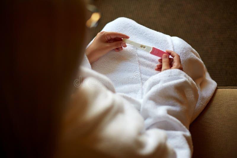 Καλλιεργημένη εικόνα της γυναίκας που κρατά μια δοκιμή εγκυμοσύνης στα γόνατά της στοκ φωτογραφίες με δικαίωμα ελεύθερης χρήσης