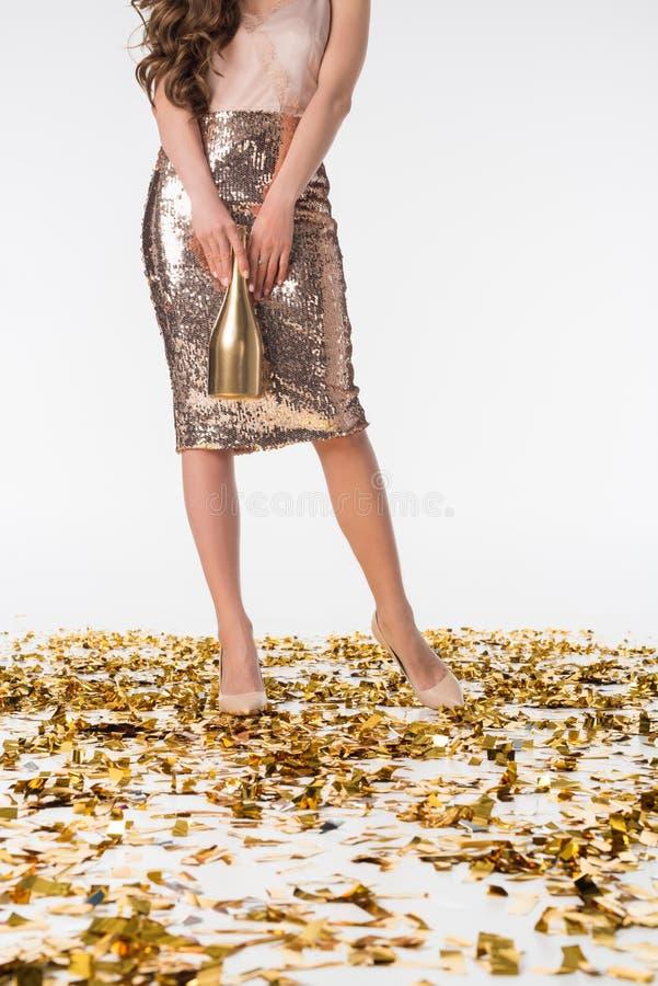 καλλιεργημένη εικόνα της γυναίκας που στέκεται στο κομφετί στην ασημένια φούστα και που κρατά το μπουκάλι στοκ φωτογραφία με δικαίωμα ελεύθερης χρήσης