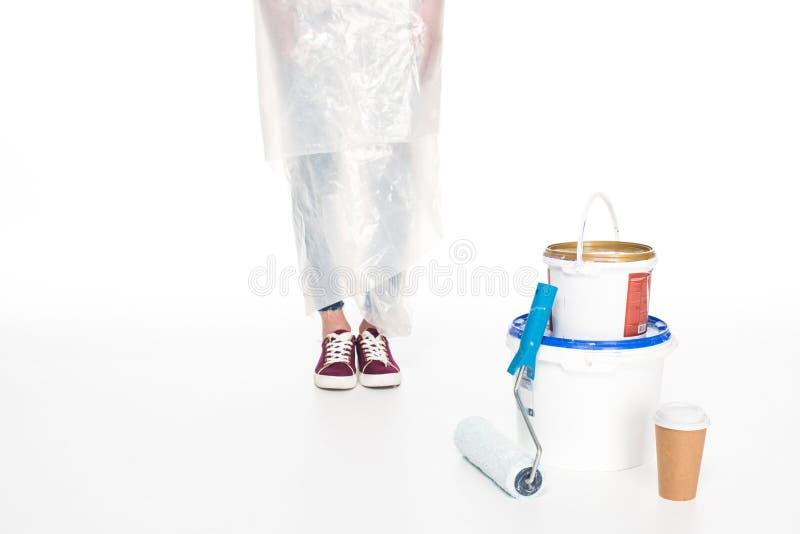 καλλιεργημένη εικόνα της γυναίκας στην κάλυψη πολυαιθυλενίου που στέκεται κοντά στους κασσίτερους χρωμάτων, τον κύλινδρο χρωμάτων στοκ εικόνες με δικαίωμα ελεύθερης χρήσης