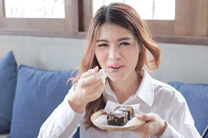 Καλλιεργημένη εικόνα της εύθυμης νέας ασιατικής γυναίκας που τρώει brownie το κέικ σοκολάτας στη καφετερία στοκ φωτογραφίες