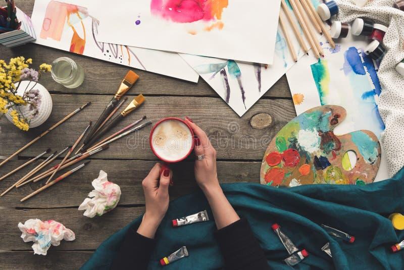 Καλλιεργημένη εικόνα του καφέ κατανάλωσης ζωγράφων στην εργασία στοκ εικόνες