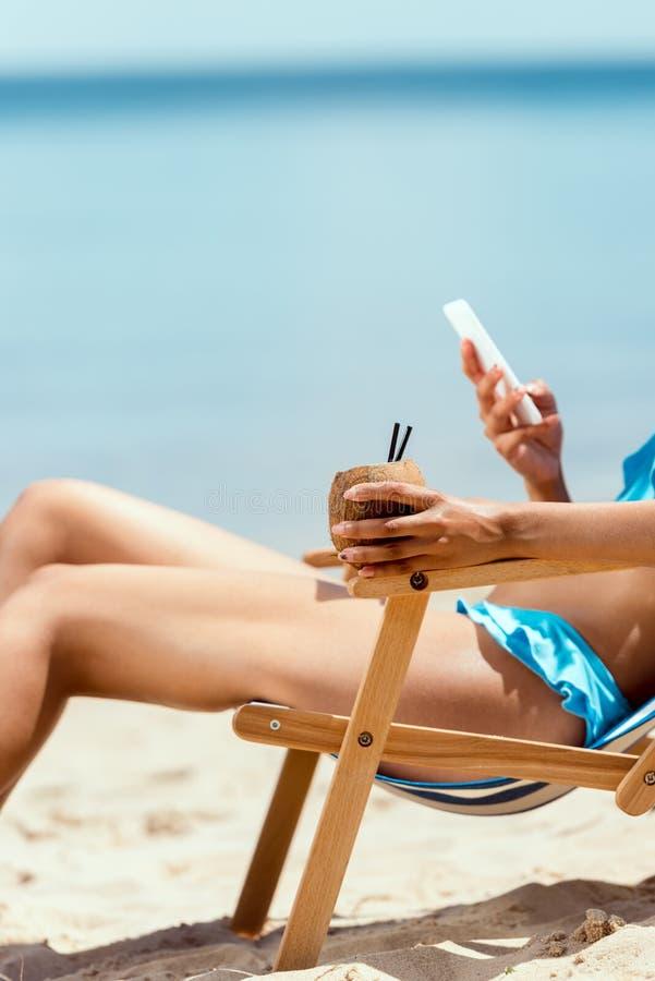 καλλιεργημένη εικόνα του κοκτέιλ εκμετάλλευσης γυναικών στο κοχύλι και χρησιμοποίηση καρύδων του smartphone βάζοντας στην καρέκλα στοκ εικόνες