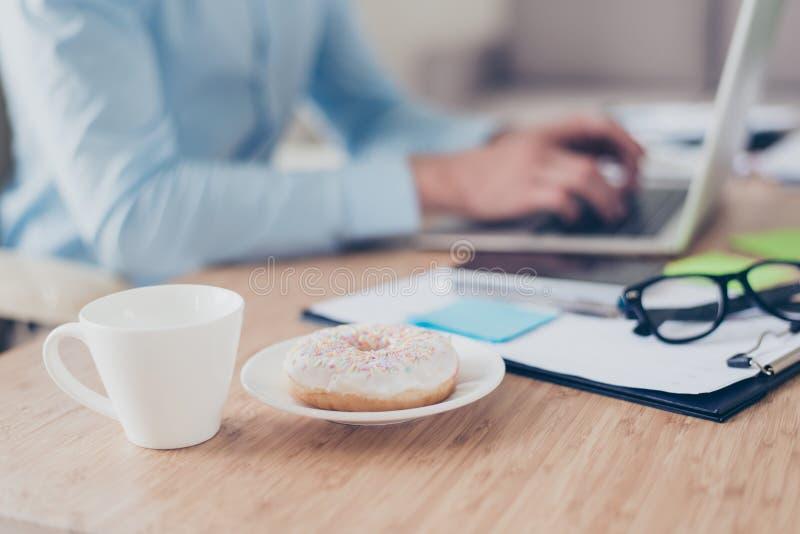 Καλλιεργημένη στενή επάνω φωτογραφία του πρόχειρου φαγητού στην εργασία, άσπρο φλυτζάνι καυτού φρέσκου στοκ εικόνες