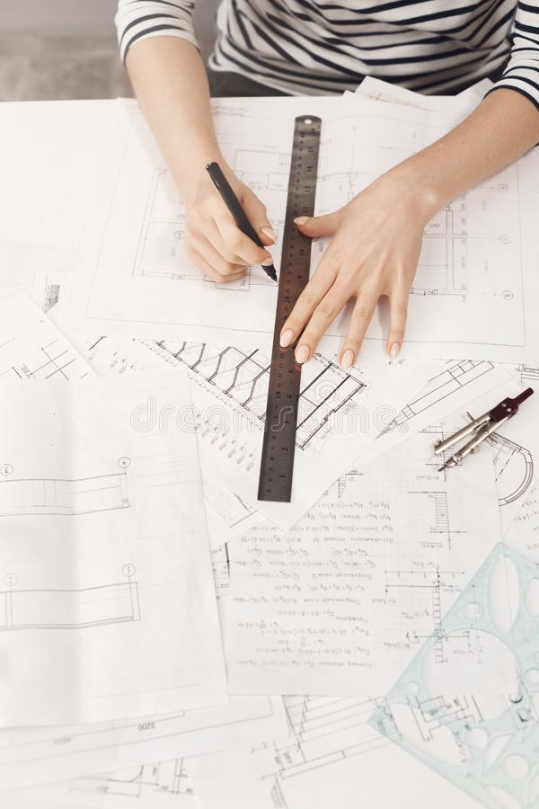 Καλλιεργημένη τοπ άποψη των νέων όμορφων θηλυκών χεριών αρχιτεκτόνων που κάνουν τα σχεδιαγράμματα με τον κυβερνήτη και τη μάνδρα  στοκ εικόνα με δικαίωμα ελεύθερης χρήσης