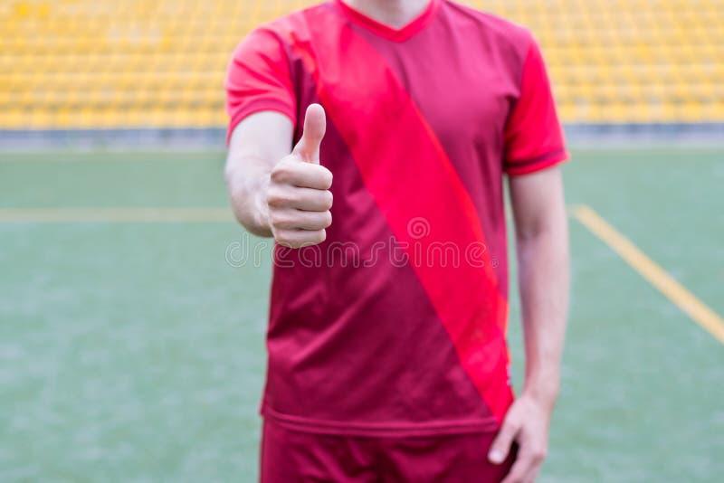 Καλλιεργημένη φωτογραφία κινηματογραφήσεων σε πρώτο πλάνο του ευτυχούς επιτυχούς ποδοσφαιριστή που παρουσιάζει δάχτυλο επάνω στο  στοκ φωτογραφίες