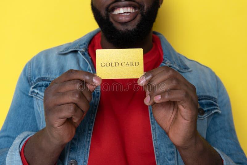 Καλλιεργημένη φωτογραφία του αφρικανικού ατόμου που κρατά τη χρυσή κάρτα στα όπλα στοκ φωτογραφίες