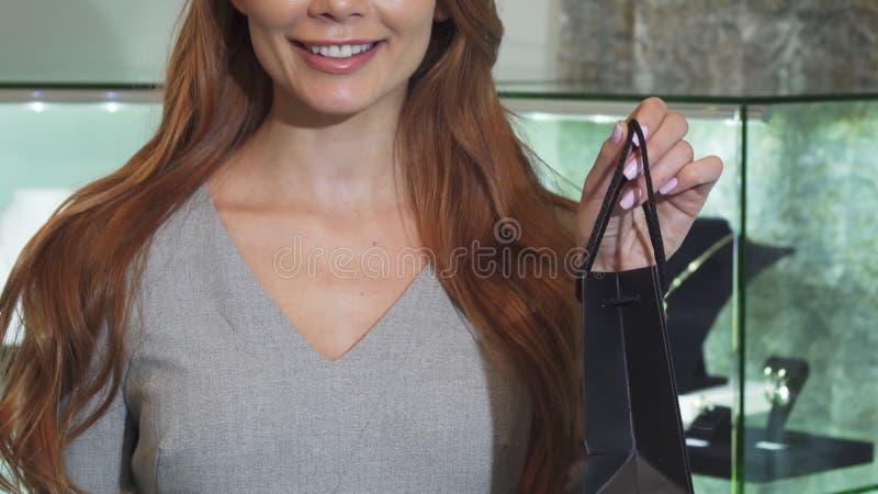 Καλλιεργημένος πυροβολισμός μιας τσάντας αγορών εκμετάλλευσης χαμόγελου γυναικών στοκ εικόνα με δικαίωμα ελεύθερης χρήσης