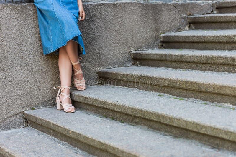 καλλιεργημένος πυροβολισμός της γυναίκας στη φούστα τζιν και τη μοντέρνη στάση παπουτσιών στοκ φωτογραφίες