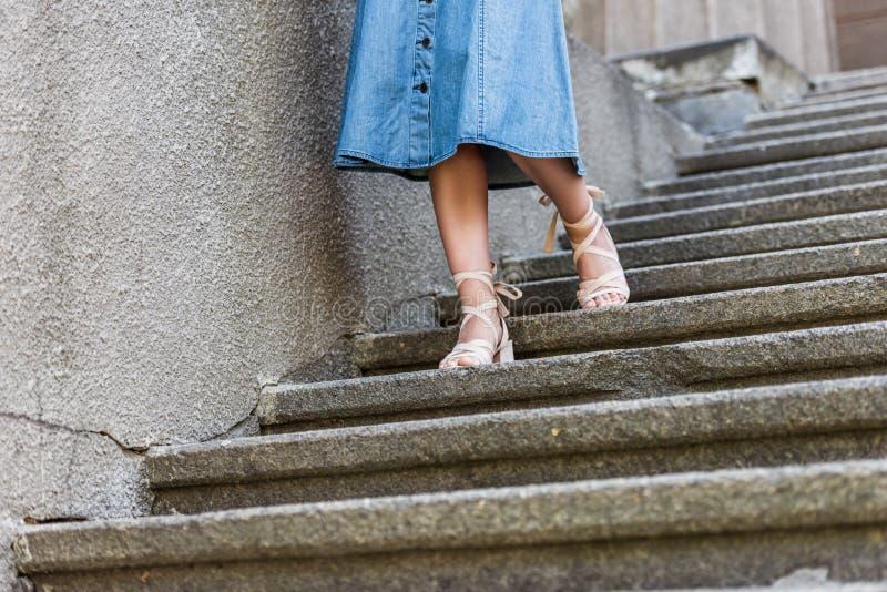 καλλιεργημένος πυροβολισμός της γυναίκας στη φούστα τζιν και το μοντέρνο περπάτημα παπουτσιών στοκ εικόνες με δικαίωμα ελεύθερης χρήσης