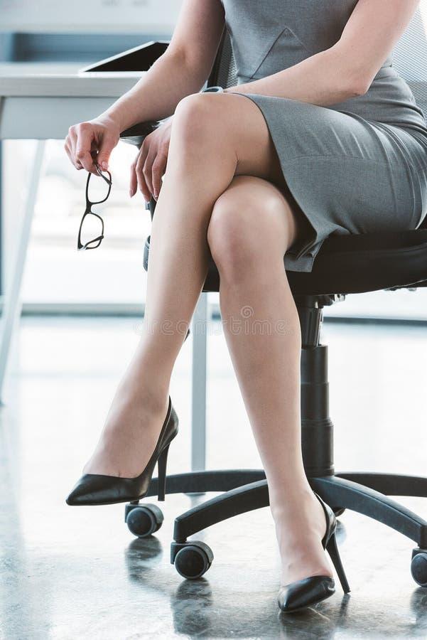 καλλιεργημένος πυροβολισμός της επιχειρηματία στα υψηλά βαλμένα τακούνια παπούτσια που κάθονται στην καρέκλα στοκ φωτογραφίες με δικαίωμα ελεύθερης χρήσης