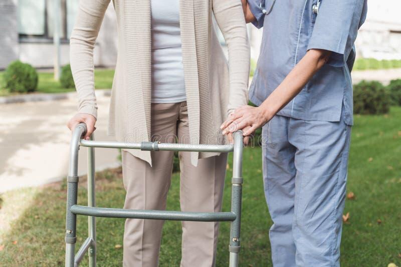 καλλιεργημένος πυροβολισμός της νοσοκόμας που βοηθά τον ανώτερο ασθενή στοκ εικόνα