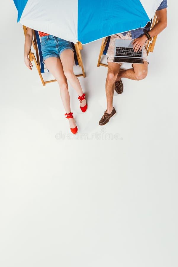 καλλιεργημένος πυροβολισμός του ζεύγους με το lap-top που στηρίζεται στις καρέκλες κάτω από την ομπρέλα παραλιών στοκ φωτογραφία με δικαίωμα ελεύθερης χρήσης