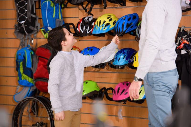 καλλιεργημένος πυροβολισμός του πατέρα και του χαμογελώντας γιου που επιλέγουν τα κράνη ποδηλάτων στο ποδήλατο στοκ φωτογραφίες με δικαίωμα ελεύθερης χρήσης