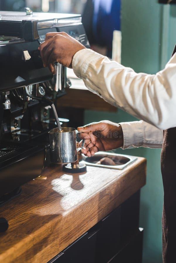 καλλιεργημένος πυροβολισμός του barista αφροαμερικάνων στην ποδιά που χρησιμοποιεί τη μηχανή καφέ στοκ εικόνες