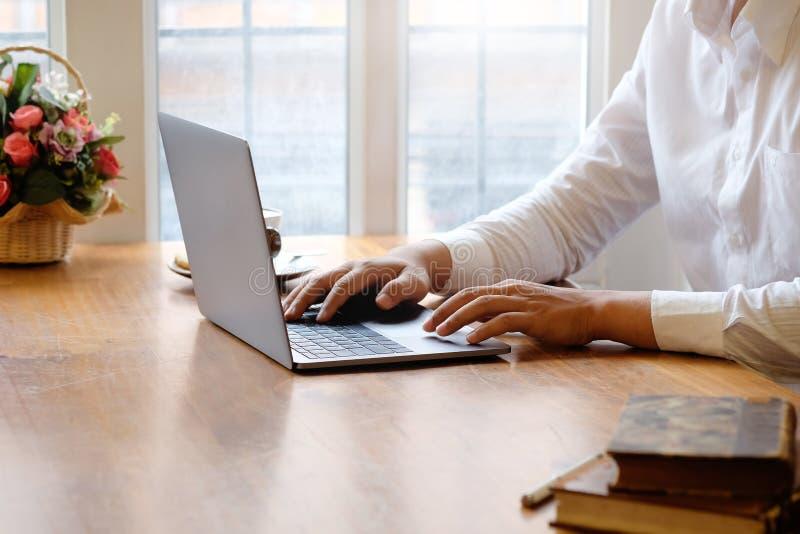 Καλλιεργημένο άτομο που χρησιμοποιεί το φορητό προσωπικό υπολογιστή και τα βιβλία με τον καφέ στο γραφείο γραφείων στοκ εικόνες με δικαίωμα ελεύθερης χρήσης
