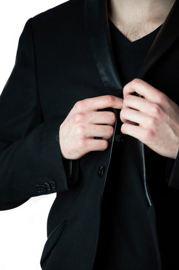 Καλλιεργημένο επικεφαλής άτομο στη μαύρη μπλούζα Β που κρατά το περιλαίμιο του σακακιού στοκ εικόνα