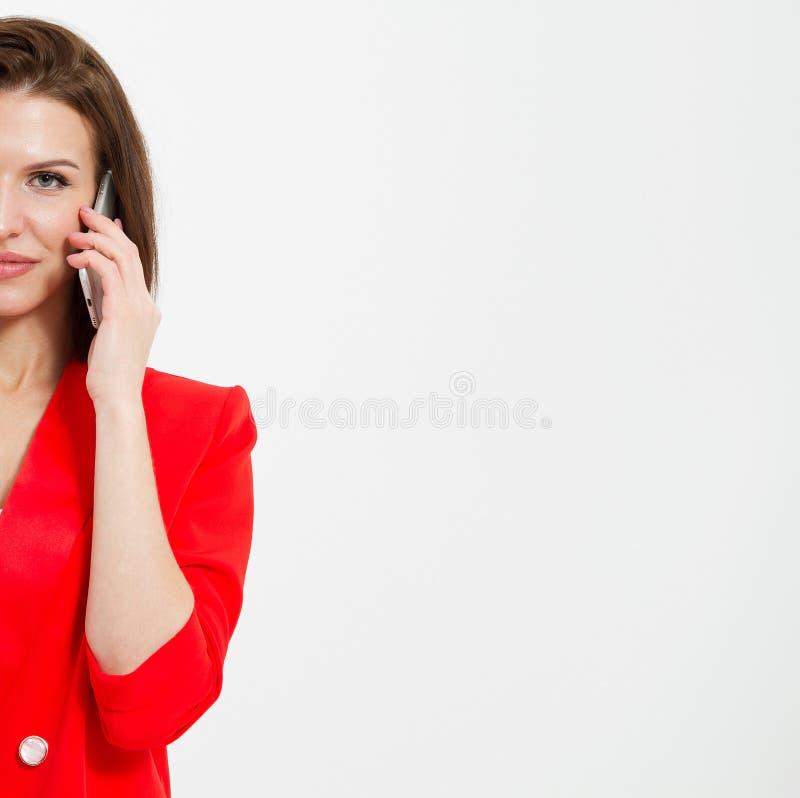 Καλλιεργημένο πορτρέτο της χαριτωμένης γυναίκας στην κόκκινη ομιλία ακολουθίας στο κινητό τηλέφωνο που απομονώνεται στο άσπρο υπό στοκ εικόνες