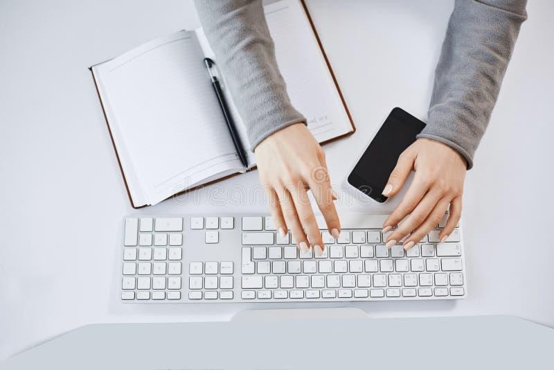 Καλλιεργημένο πορτρέτο των χεριών γυναικών που δακτυλογραφούν στο πληκτρολόγιο και που λειτουργούν με τον υπολογιστή και τις συσκ στοκ εικόνα