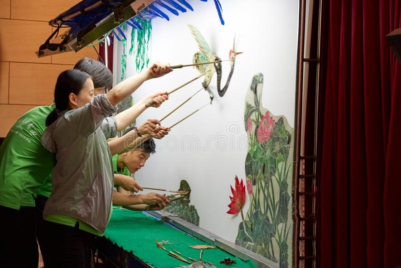 Καλλιτέχνες την ώρα της παράστασης το κινεζικό παιχνίδι σκιών στοκ εικόνα με δικαίωμα ελεύθερης χρήσης