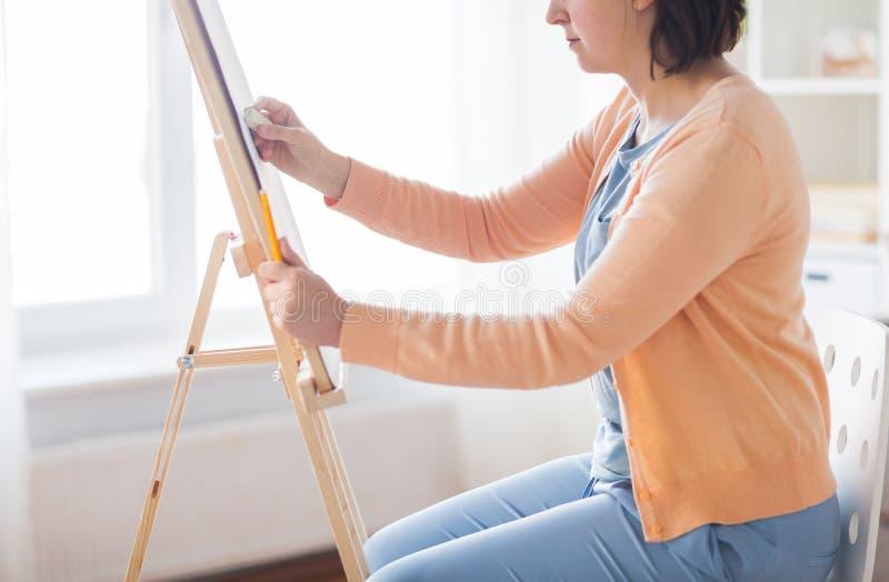 Καλλιτέχνης με τη γόμα και easel στο στούντιο στοκ εικόνες
