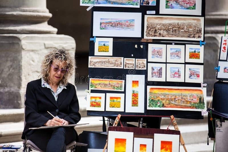 Καλλιτέχνης που πωλεί την εργασία της στο προαύλιο της στοάς Uffizi στη Φλωρεντία στοκ εικόνες