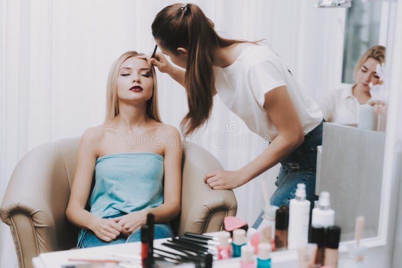 Καλλιτέχνης Makeup και πρότυπη συνεδρίαση στην έδρα στο σαλόνι στοκ φωτογραφίες με δικαίωμα ελεύθερης χρήσης