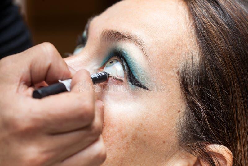 Καλλιτέχνης Makeup που περιγράφει τα μάτια λευκών γυναικών στοκ εικόνα