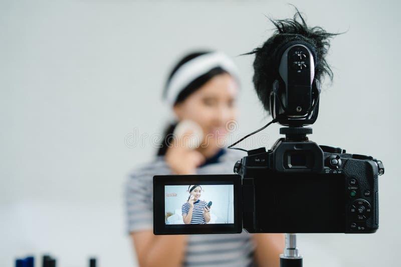 Καλλυντικά ομορφιάς ομορφιάς blogger παρόντα καθμένος στην μπροστινή κάμερα για το βίντεο καταγραφής Όμορφη σκόνη χρήσης γυναικών στοκ φωτογραφία