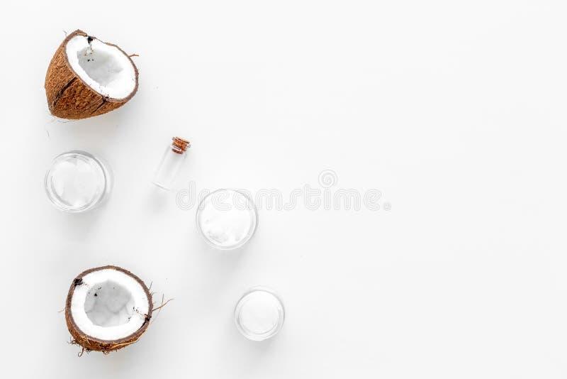Καλλυντικά πετρελαίου καρύδων για τη φροντίδα δερμάτων και τρίχας Πετρέλαιο στο μικρό μπουκάλι, βάζο κρέμας, halfs της καρύδας με στοκ εικόνα