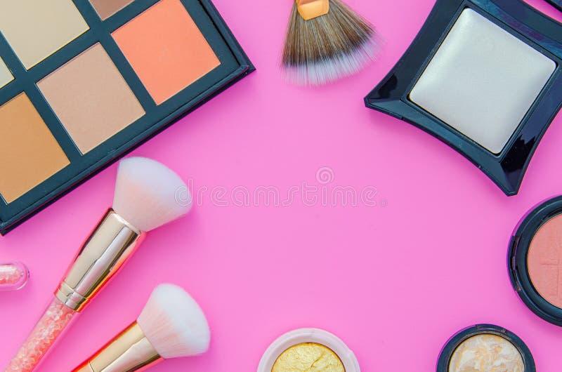 Καλλυντικά που τίθενται στο ρόδινο υπόβαθρο Το πλαίσιο Makeup έκανε από τις βούρτσες για τη σκόνη σύνθεσης, blusher, διορθωτές γι στοκ εικόνες