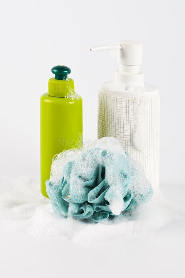 Καλλυντικά προϊόντα λουτρών, πράσινοι σφουγγάρι και αφρός στο ελαφρύ υπόβαθρο στοκ φωτογραφία με δικαίωμα ελεύθερης χρήσης