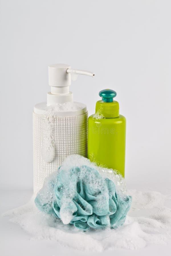 Καλλυντικά προϊόντα λουτρών, πράσινοι σφουγγάρι και αφρός στο ελαφρύ υπόβαθρο στοκ εικόνα