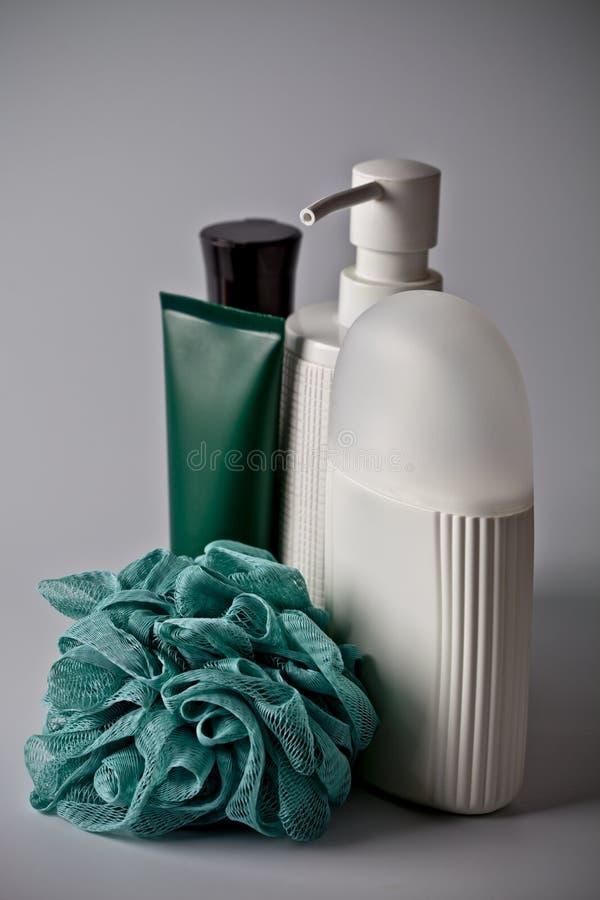 Καλλυντικά προϊόντα λουτρών: το υγρό σαπούνι, ο αφρός λουτρών, creme και το τυρκουάζ σφουγγίζουν στο ελαφρύ υπόβαθρο στοκ εικόνα