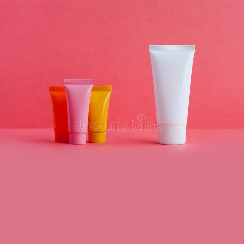 Καλλυντικοί σωλήνες υγιεινής στο ρόδινο υπόβαθρο Άσπρο ρόδινο πορτοκαλί κίτρινο χρώμα τεσσάρων κενό πλαστικών εμπορευματοκιβωτίων στοκ φωτογραφία