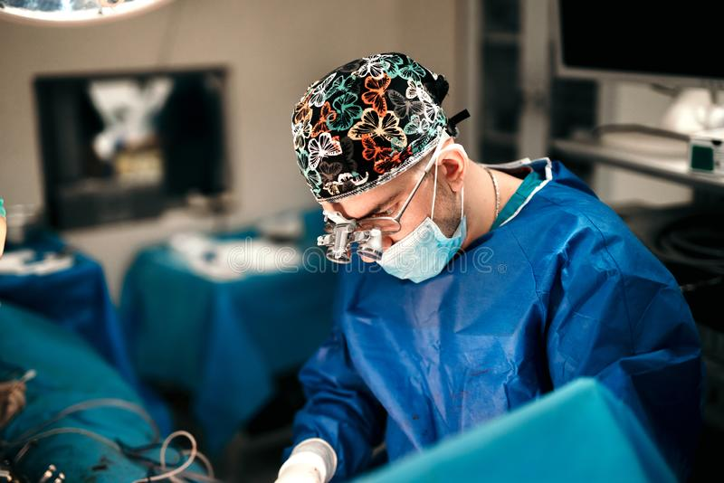 Καλλυντικός ειδικός χειρούργων που εκτελεί τη χειρουργική επέμβαση στηθών στο λειτουργούν δωμάτιο νοσοκομείων στοκ εικόνα