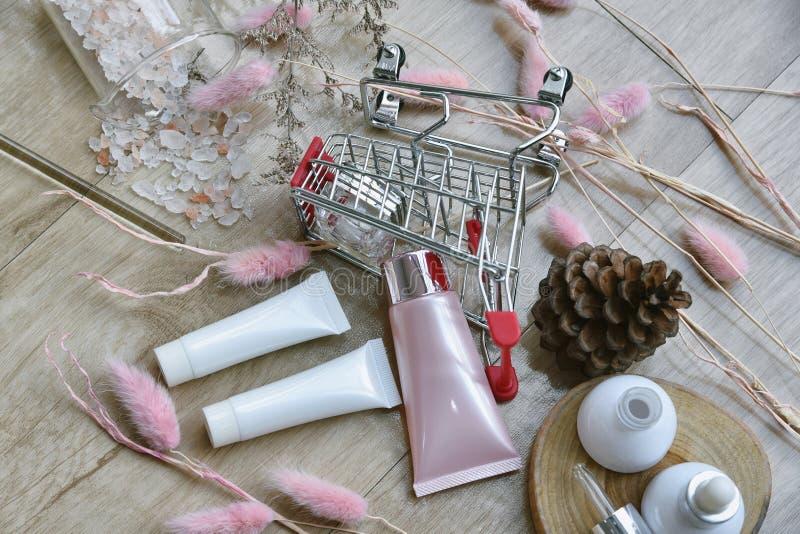 Καλλυντικό εμπορευματοκιβώτιο μπουκαλιών στο κάρρο αγορών, το προϊόν ομορφιάς και makeup on-line την προώθηση πώλησης με το κενό  στοκ εικόνες