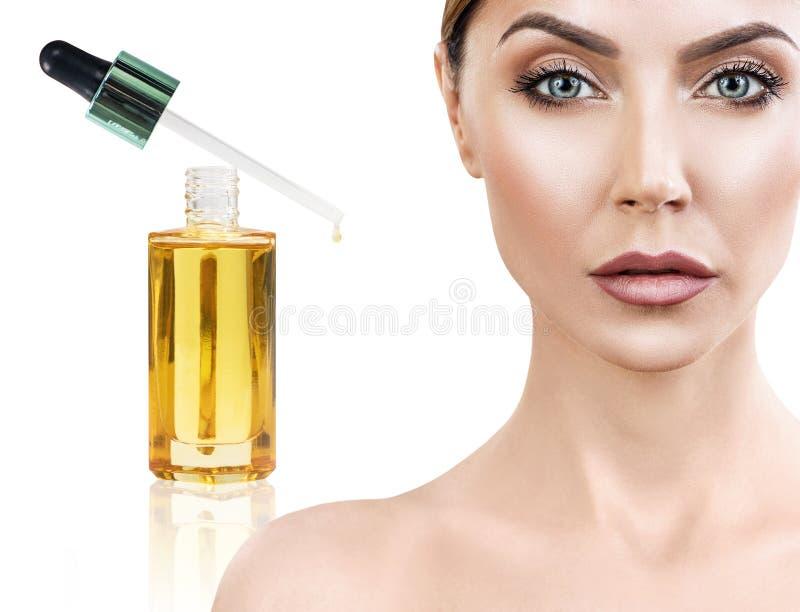 Καλλυντικό πετρέλαιο που ισχύει στο πρόσωπο της νέας γυναίκας στοκ εικόνες
