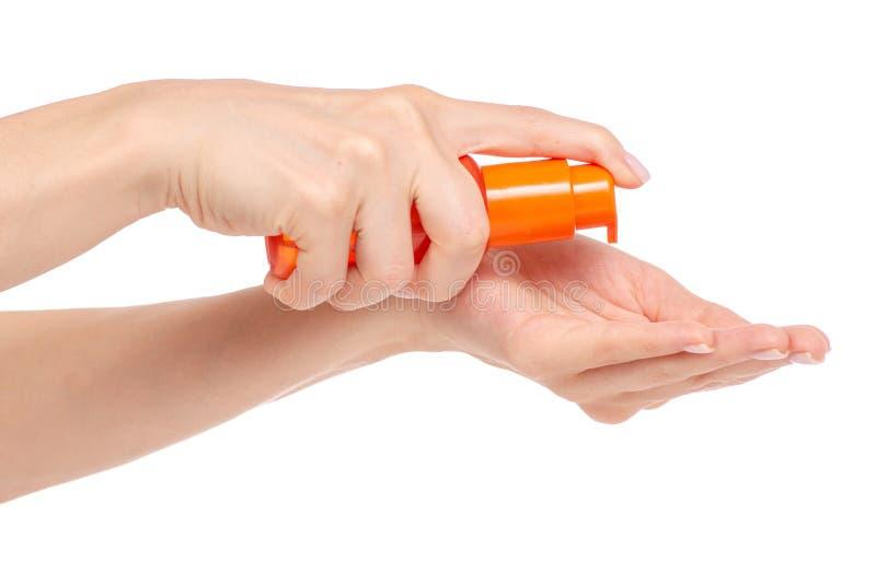 Καλλυντικό πορτοκαλί μπουκάλι με το διαθέσιμο σώμα τρίχας πηκτωμάτων πετρελαίου χεριών διανομέων στοκ εικόνες