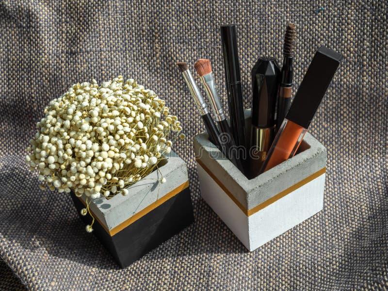 Καλλυντικό σύνολο και ξηρό λουλούδι στο κυβικό συγκεκριμένο εμπορευματοκιβώτιο μορφής στοκ εικόνες με δικαίωμα ελεύθερης χρήσης