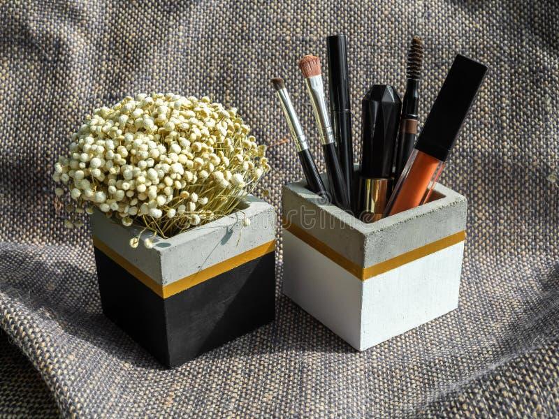 Καλλυντικό σύνολο και ξηρό λουλούδι στο κυβικό συγκεκριμένο εμπορευματοκιβώτιο μορφής στοκ φωτογραφίες
