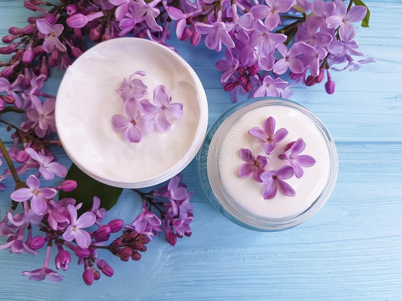 Καλλυντικό φρέσκο ιώδες λουλούδι αποσπασμάτων επεξεργασίας κύπελλων κρέμας moisturizer σε ένα μπλε ξύλινο υπόβαθρο στοκ εικόνες με δικαίωμα ελεύθερης χρήσης