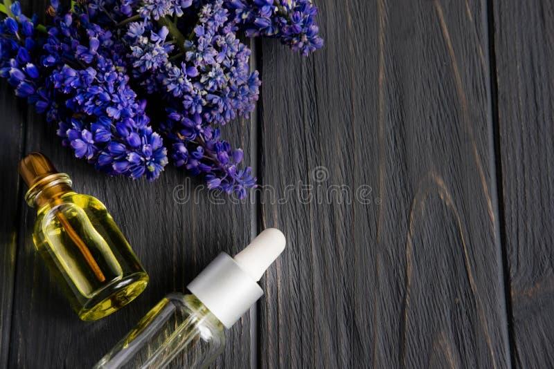 Καλλυντικό olia σε ένα σκοτεινό ξύλινο υπόβαθρο με τα ιώδη λουλούδια Υπόβαθρο SPA για το σαλόνι ομορφιάς E r στοκ εικόνες με δικαίωμα ελεύθερης χρήσης