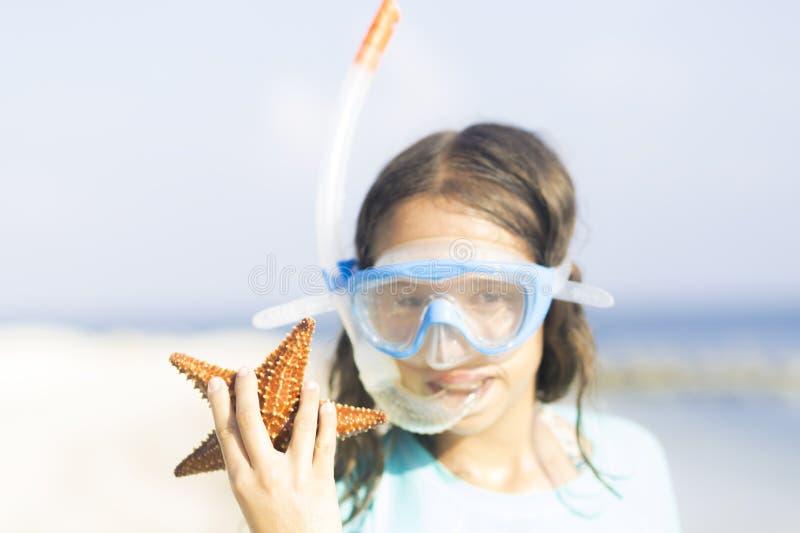 Καλοκαίρι, ευτυχές κορίτσι με τον όμορφο αστερία στοκ εικόνες