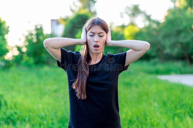 Καλοκαίρι κοριτσιών στο καθαρό αέρα Έκλεισα τα αυτιά μου με τα χέρια μου και άνοιξα το στόμα μου Συγκινήσεις του δυνατού θορύβου  στοκ φωτογραφία με δικαίωμα ελεύθερης χρήσης