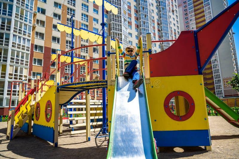Καλοκαίρι, παιδική ηλικία, ελεύθερος χρόνος, φιλία και έννοια ανθρώπων - το ευτυχές μικρό παιδί στην παιδική χαρά παιδιών γλίστρη στοκ εικόνες