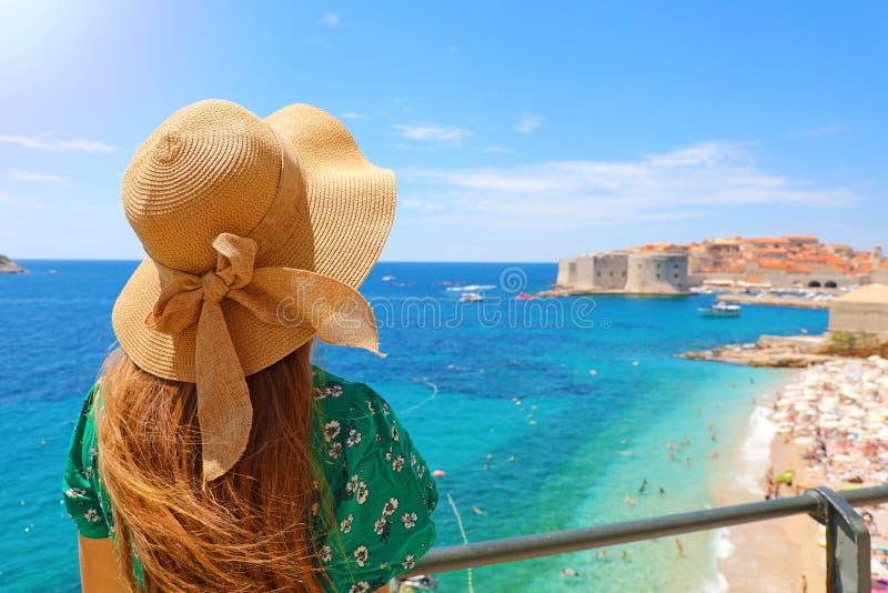 Καλοκαιρινές διακοπές στην Κροατία Πίσω άποψη της νέας γυναίκας με το καπέλο αχύρου και του πράσινου φορέματος με την παλαιά πόλη στοκ εικόνες