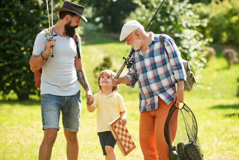 Καλοκαιρινό σαββατοκύριακο Ευτυχισμένος παππούς, πατέρας και εγγονός με καλάμια ψαρέματος Άνγκλερς Ημέρα των ανδρών Αλιεία στοκ φωτογραφία