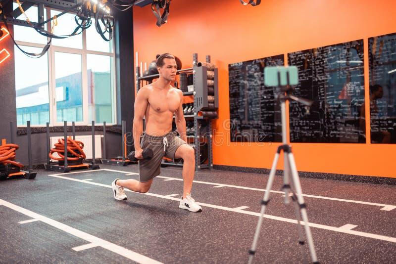 Καλοχτισμένο άτομο της Νίκαιας που παρουσιάζει την άσκηση με τα dumbells στοκ εικόνα
